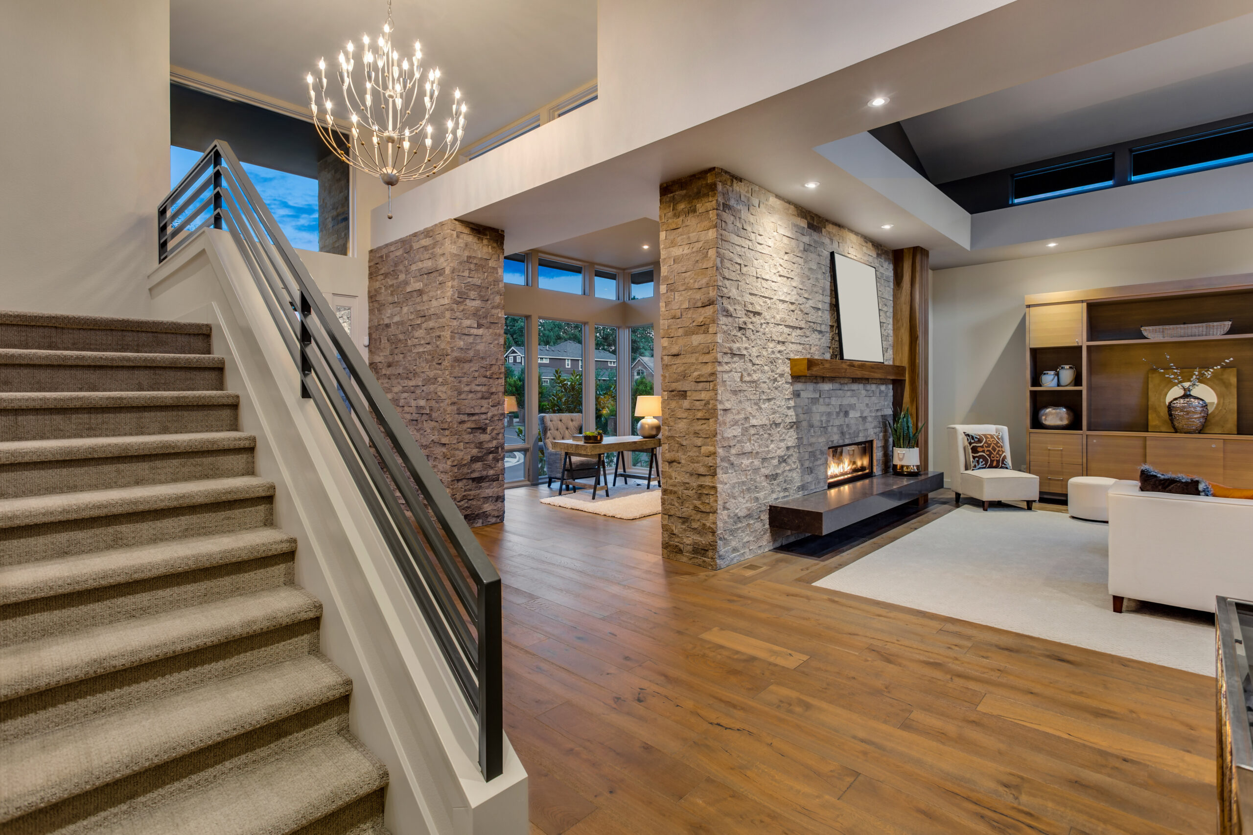 Spacious new luxury home interior in luxury home with large stone fireplace, roaring fire, view of den and staircase.