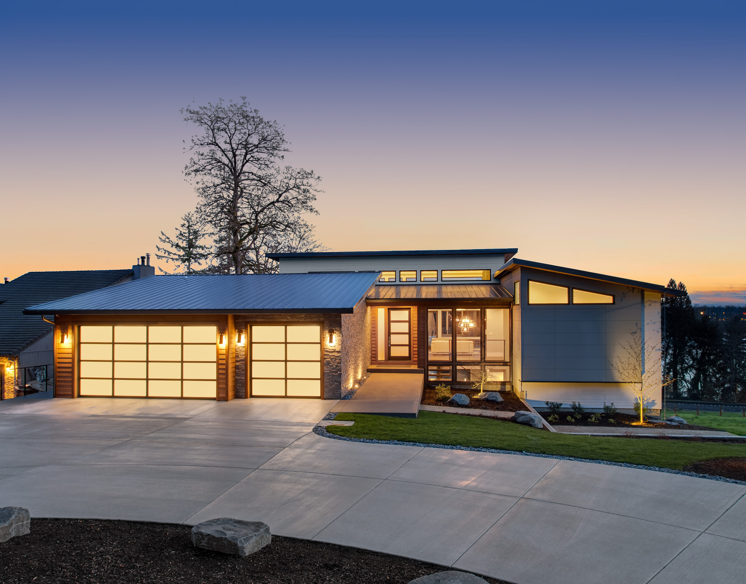Beautiful modern style luxury home exterior at sunset with glowing interior lights. Features three car garage with translucent panels, clerestory windows and elegant design.